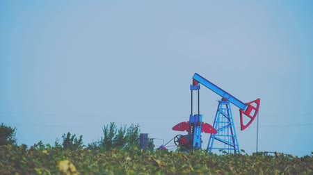 zvedák : The oil pump, industrial equipment. Operating oil and gas well in European oil field, profiled on blue sky with cumulus clouds.