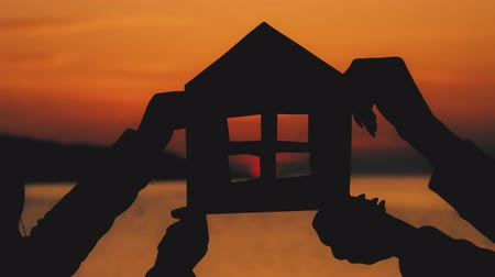 caseiro : Silhouette a small paper house made of cardboard is held with hands against on sea sunset. Efficiency and home concept - close up of hands holding paper house. The concept of home loans and mortgages.