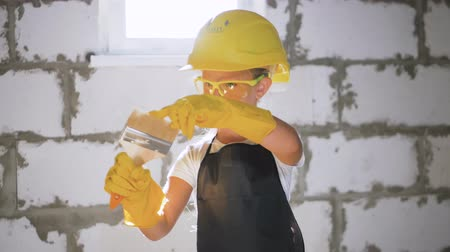 repairer : Beautiful little girl in helmet with tools. Building, development, construction and architecture concept - smiling little girl in yellow helmet.
