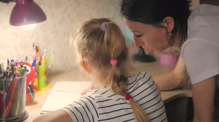 encouraging : Young mother helps her daughter with her homework at on the table under the light of a lamp.