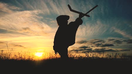 aviador : Cute child playing with toy wooden airplane in the field at sunset time. Silhouette of kid playing wooden plane in nature. Relax time on holiday concept travel and freedom. Archivo de Video