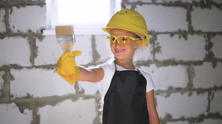 ремонтник : Beautiful little girl in helmet with tools. Building, development, construction and architecture concept - smiling little girl in yellow helmet.