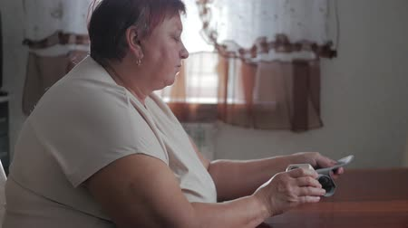 hypertension : Mature obese women measuring pressure with digital sphygmomanometer while sitting at table. Senior woman is taking care for health with hearth beat monitor. Healthcare and medical concept. Stock Footage