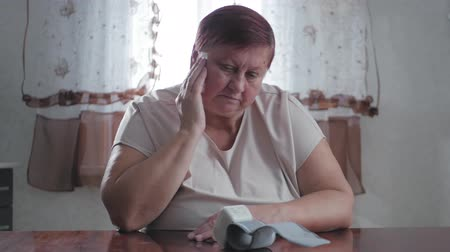 sphygmomanometer : Mature obese women measuring pressure with digital sphygmomanometer while sitting at table. Senior woman is taking care for health with hearth beat monitor. Healthcare and medical concept. Stock Footage