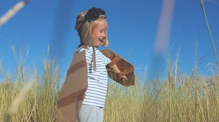 ser : Girl playing to be a classic pilot, wearing a fur hat, glasses and wings made of cardboard as a toy. Child with cardboard wings jumping in field. Little kid play in cardboard plane, childhood.