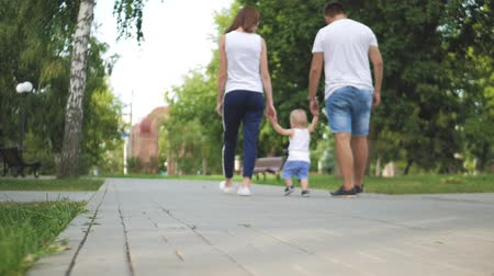 neşeli : Father and Mother with son holding hand in the park. Family walk in the park. Stok Video