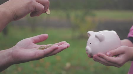экономить : Mother and daughter child putting coins into piggy bank. Woman holds piggy bank while girl puts coins inside outdoor, lifestyle. Concept kid saving money for future.