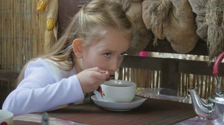 cacau : Cute little girl drinking tea in cafe. light breakfast. Little caucasian girl taking a sip of tea at the cafe. Vídeos