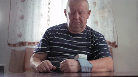 nadciśnienie : Senior man taking his blood pressure at home on the table. Men health check blood pressure.and heart rate with digital pressure gauge standard blood pressure test results .Health and Medical concept.