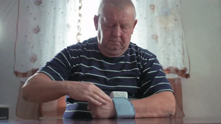 rozchod : Senior man taking his blood pressure at home on the table. Men health check blood pressure.and heart rate with digital pressure gauge standard blood pressure test results .Health and Medical concept.