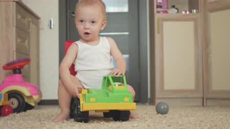 playful infant : Lovely baby boy playing with a big car toy on floor at home. Kid boy toddler playing with toy car indoors. Future driver. Funny toddler boy indoors.