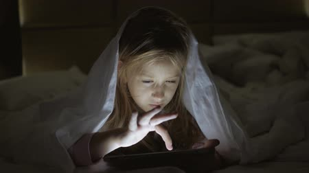 érdekes : Young woman mom and her daughter watching interesting film together on tablet and laugh under the blanket. Funny mom and lovely child are having fun with tablet. Happy loving family. Stock mozgókép