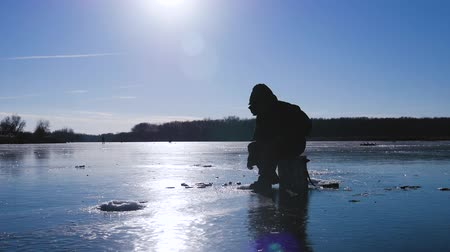 frozen lake : Winter fishing. Fisherman on a lake at winter sunny day. Stock Footage