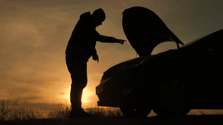 толчок : Silhouette man is checking engine bay of the broken down car while sunset. Стоковые видеозаписи