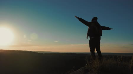 emelt : Silhouette of person in mountain. Young man with backpack standing with raised hands on top of a mountain. Sport and active life.