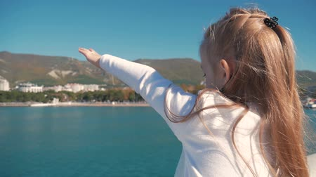 emelt : Cute girl happily raised his hand up welcoming the sea. Stock mozgókép