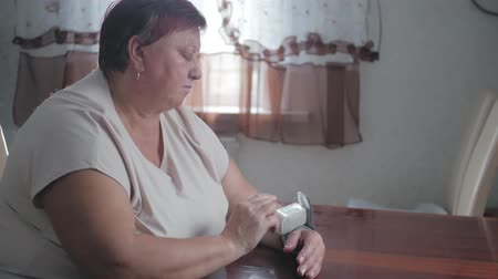nadciśnienie : Mature obese women measuring pressure with digital sphygmomanometer while sitting at table. Senior woman is taking care for health with hearth beat monitor. Healthcare and medical concept. Wideo