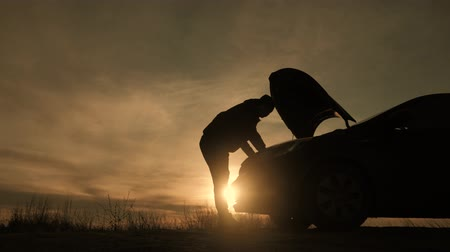 quebrado : Silhouette man is checking engine bay of the broken down car while sunset. Vídeos