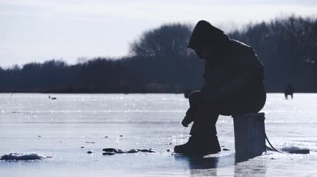 fly fishing : Silhouette fisherman on ice at frozen lake in winter. Winter holidays and people hobby concept.