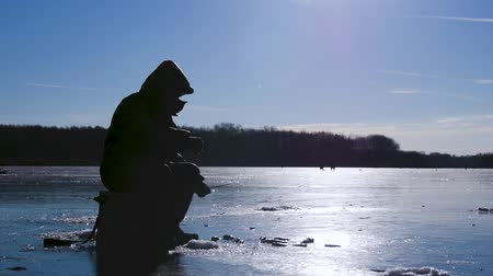 tyč : Silhouette fisherman on ice at frozen lake in winter. Winter holidays and people hobby concept.