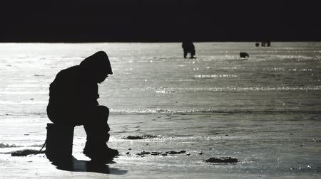 gestreept : Silhouette fisherman on ice at frozen lake in winter. Winter holidays and people hobby concept.
