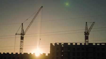 vinç : Crane and building construction site at sunset. Silhouette workers on a background of the sky. Stok Video