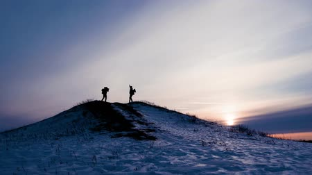 hiking : Two travellers silhouette with backpacks show each other the cameras during winter hike in the mountains, mountaineer photographs in the mountains in winter, tourist in mountains with the camera.