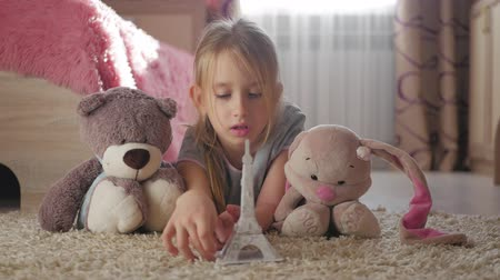 eiffel : Little girl with her toys at children room dreaming about travel to Paris. Child dream, vacation and travel concept.