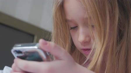 phablet : Young girl sitting on the bed and makes online shopping on a phone. Online shopping concept. Stock Footage