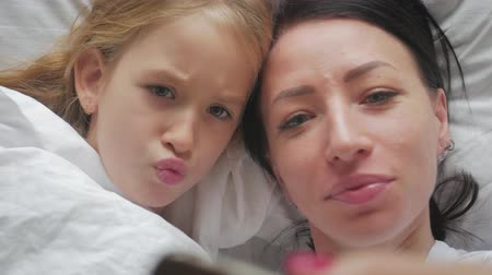 спальня : Young beautiful mother and her cute daughter taking selfie with smartphone and smiling while lying on the bed at home. Woman taking selfie with a little girl in bedroom.
