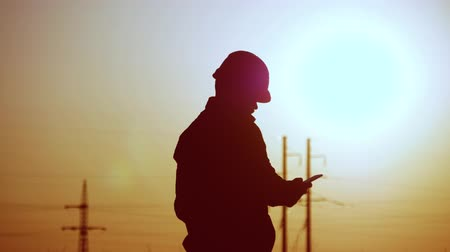パイロン : silhouette of engineer electricity talking and use phone during sunset