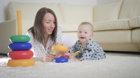 babysitter : Joyful mother and baby playing with toys on a carpet at home. Side view of a happy mother and son playing with toys on the floor. Happy family spend fun time together. Stock Footage