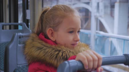 okno : Little girl is looking through window while sitting in train.