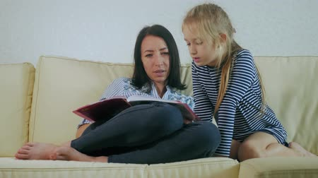 物語 : Mother and young daughter reading book on couch at home. Time only for mother and her little daughter.