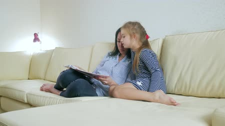 olvasás : Mother and young daughter reading book on couch at home. Time only for mother and her little daughter.