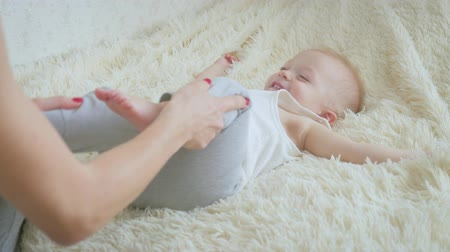 gymnastics : Mother massaging little son in bed at home. Strengthening exercises for babies, home healthcare concept.