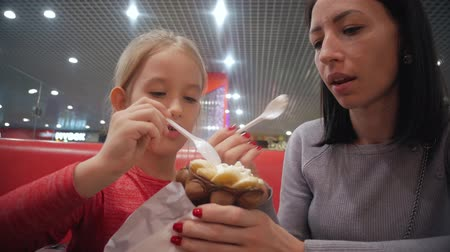 конусы : Young mother and daughter eat ice cream in a cafe. Good relations of parent and child. Happy moments together. Family lifestyle.
