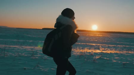 tourist silhouette : Silhouette of a young happy girl traveler with a backpack go at sunset, winter travel, lifestyle, freedom concept. Stock Footage