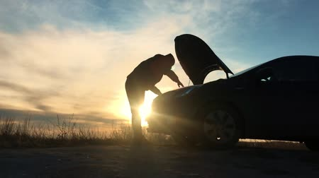 meteliksiz : Silhouette man is checking engine bay of the broken down car while sunset. Stok Video