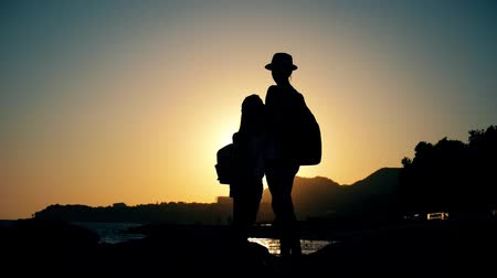 bordas : Silhouettes of mother and child tourists hiking at sunset. Mom and daughter on summer vacation carrying backpacks. Little girl following her mom on cliff edge. The concept of traveling with children. Stock Footage