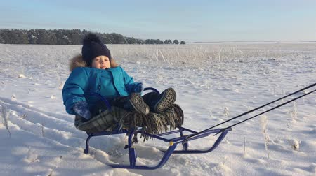 Little boy enjoying a sleigh ride. Baby on the sleigh. Children play outdoors in snow. Cheerful winter vacation. Winter fun.