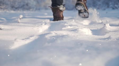 Lonely man walking in the snow, close up man shoes. Walking concept. Slow motion. Стоковые видеозаписи