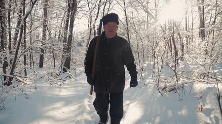 Hunter walking in the snowy winter forest. Winter hobby, sun, hunting concept. Стоковые видеозаписи