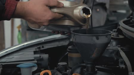 Car maintenance servicing mechanic pouring new oil lubricant into the car engine. Pouring fresh new clean synthetic oil into car engine. Change engine oil of your car. Стоковые видеозаписи