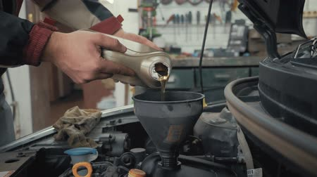 воронка : Car maintenance servicing mechanic pouring new oil lubricant into the car engine. Pouring fresh new clean synthetic oil into car engine. Change engine oil of your car. Стоковые видеозаписи