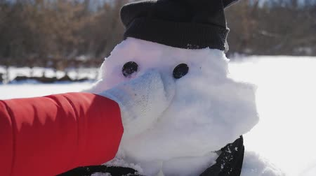 Girl inserts a nose on the snowman. The child plays with a snowman. Winter happy time, kid on snow.
