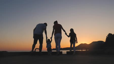 Silhouette of active family having fun and enjoying togetherness on the beach at sunset.
