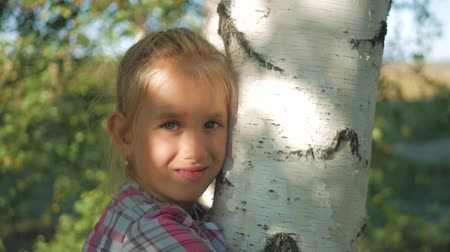 Teen girl leaning against a birch tree in the sun. Close up, looking at camera.
