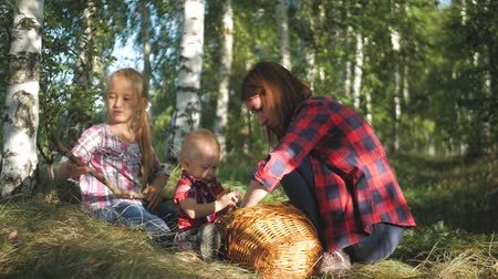 Mother with kids going on mushrooms picking in forest.