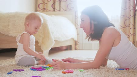 Joyful mother and baby playing with toys on a carpet at home. Side view of a happy mother and son playing with toys on the floor. Happy family spend fun time together. Стоковые видеозаписи